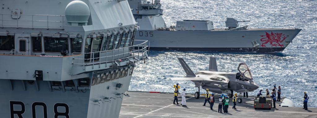 Flight deck of HMS Queen Elizabeth - HMS Dragon in background